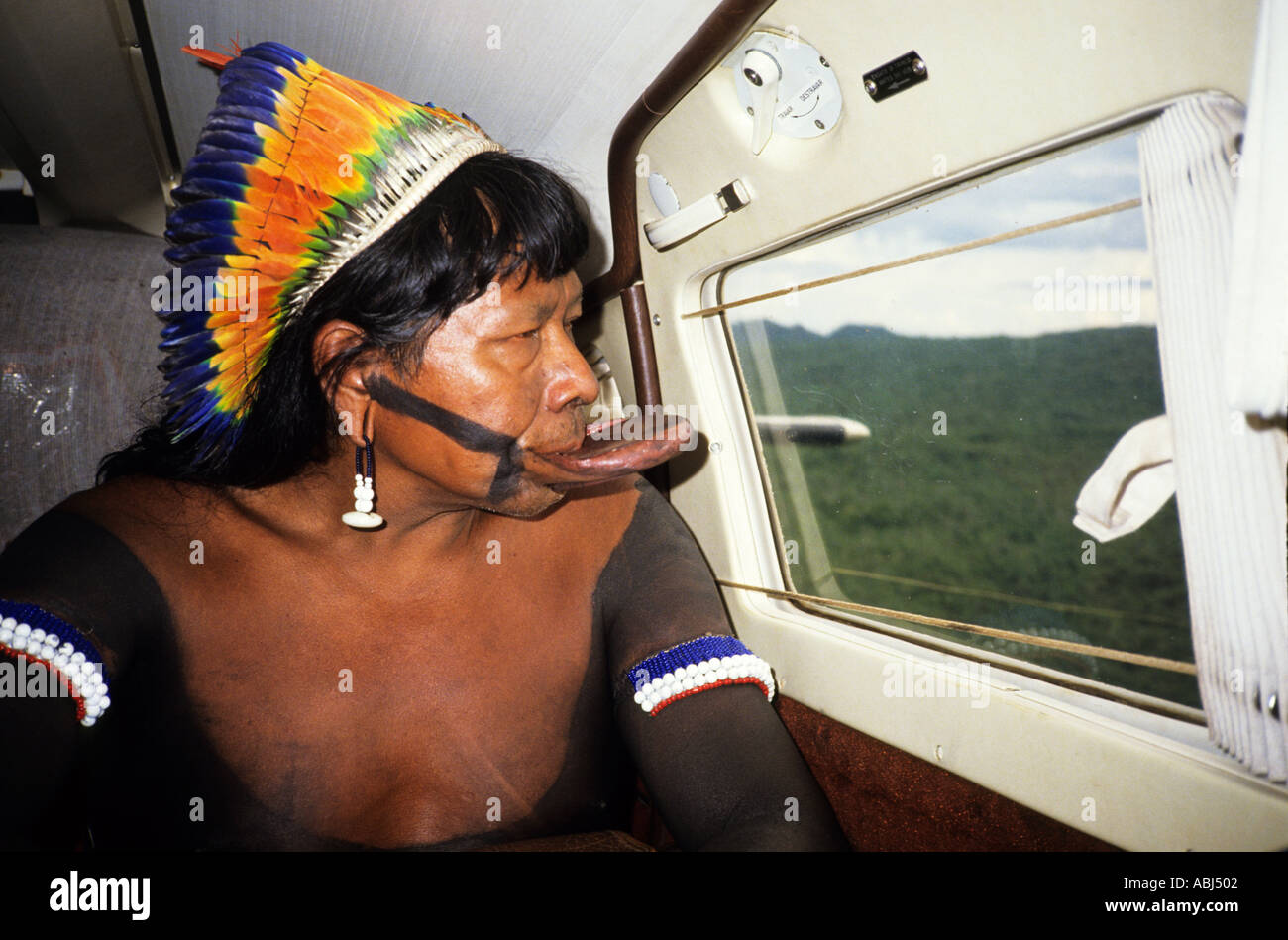 Amazon, Brazil. Chief Raoni of the Megranoti (Kayapo Nation) with botoque and feather cocar headdress in an airplane. - Stock Image