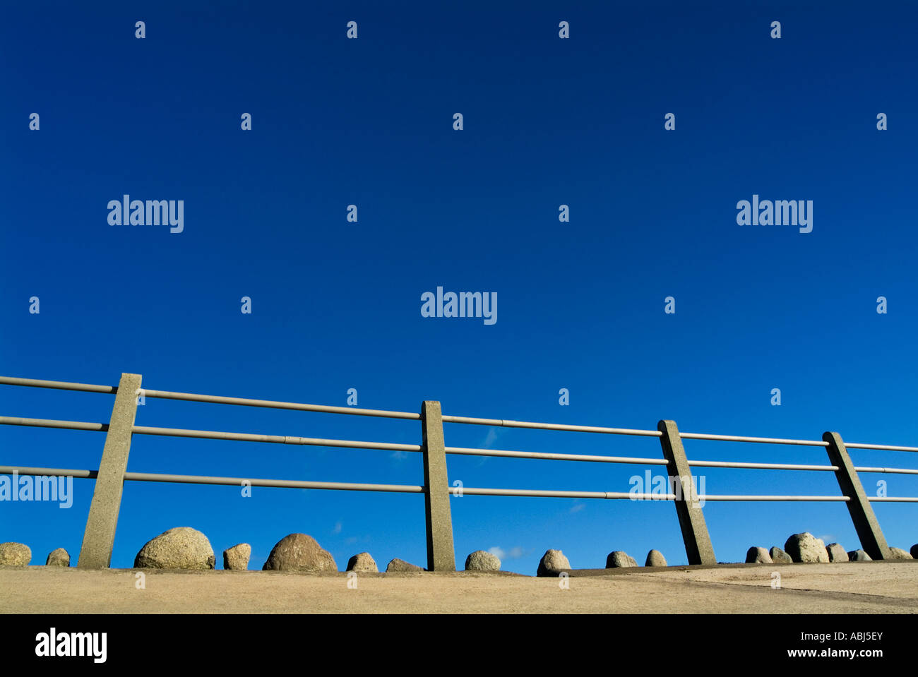 An unusual graphic art image of a metal pole fence and some rocks set against a deep blue sky exaggerated by wide - Stock Image