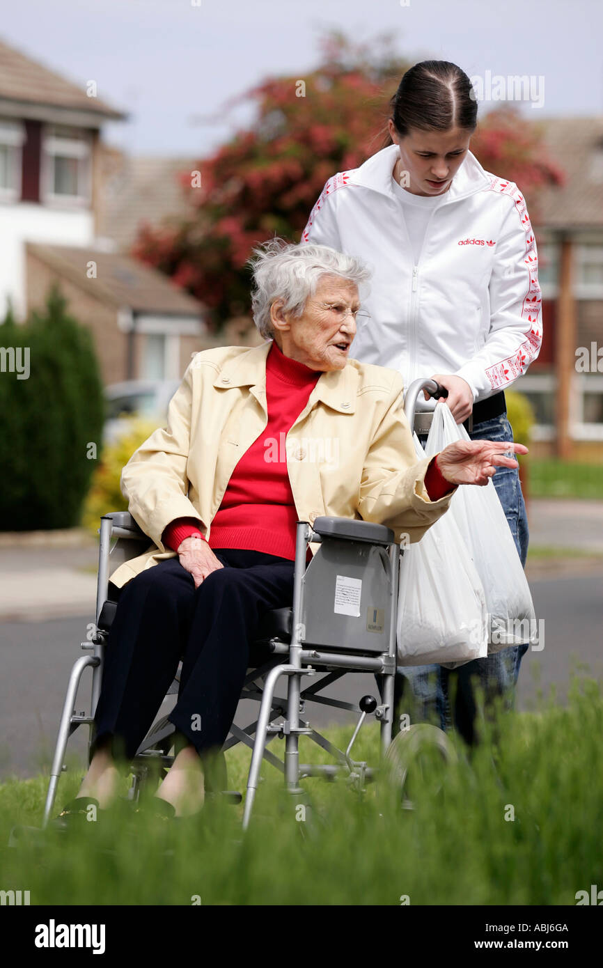 teenager helping old lady in wheel chair Stock Photo