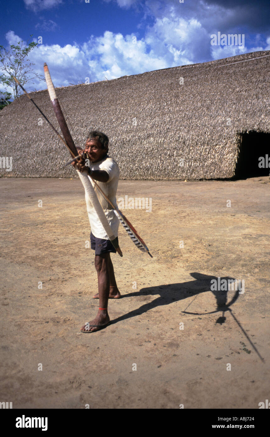 Koatinemo village, Brazil. Assurini Indian man demonstrating his bow and arrow skills outside the House of the Dead. Para State. - Stock Image