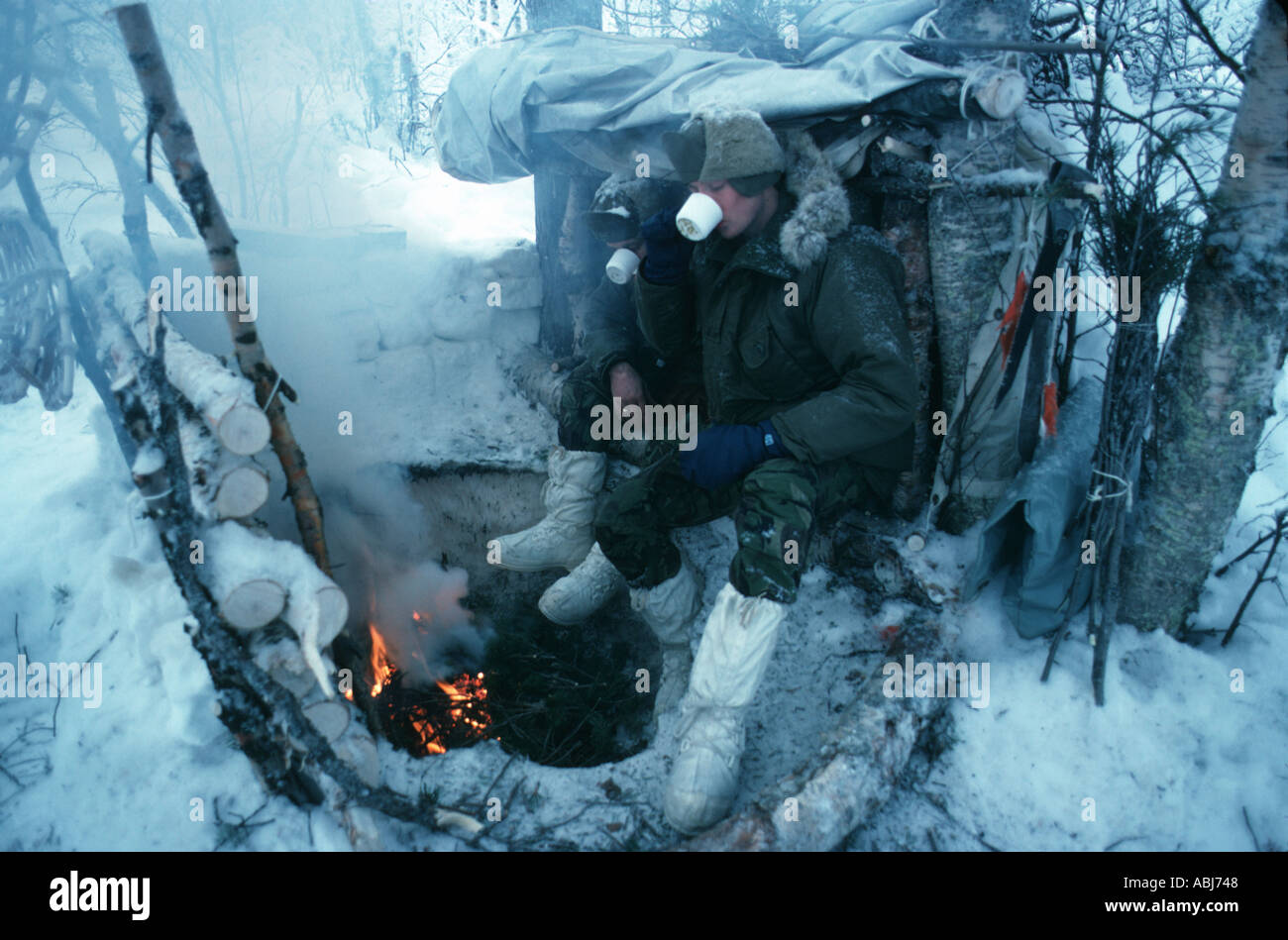 Soldiers on survival exercise in arctic circle keeping warm with fire - Stock Image