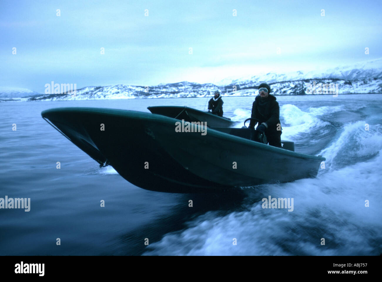 Mountain and Arctic Warfare with rigid raider boat on fjord - Stock Image