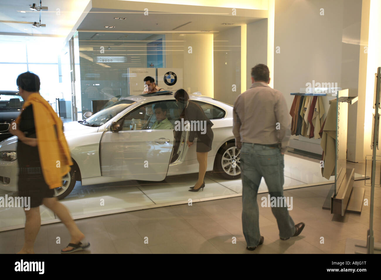 Prospective BMW buyers survey the latest model in Bangkok s new upmarket shopping centre Paragon - Stock Image