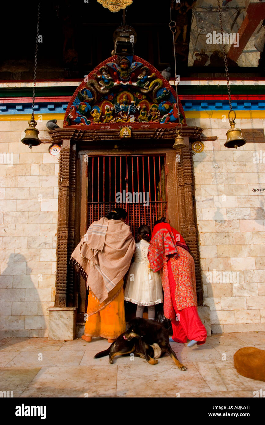 Women peer into a Hindhu Temple in the old quarter of Kathmandhu-Durbar square. - Stock Image