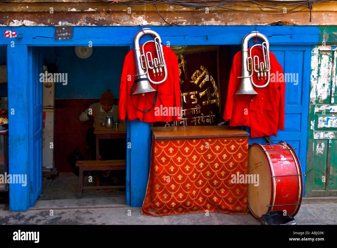A wedding band musician takes a break in a traditional tea & curry shop in Durbar Square, Kathmandu's old town. - Stock Image