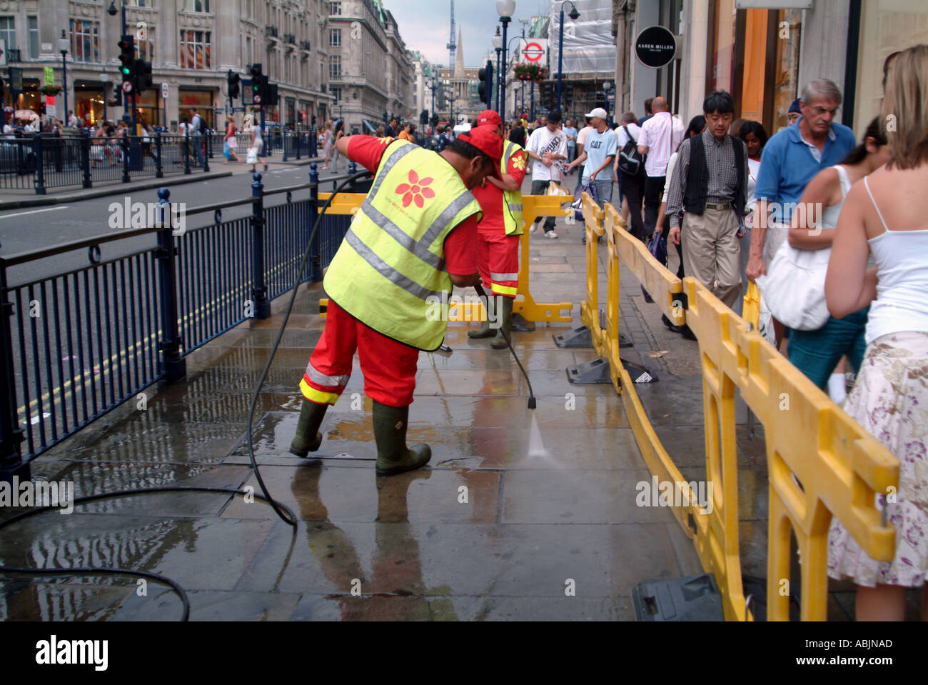 CITY COUNCIL WORKERS WASHING UP THE STREET WITH COMPRESSED WATER LONDON 2005 - Stock Image