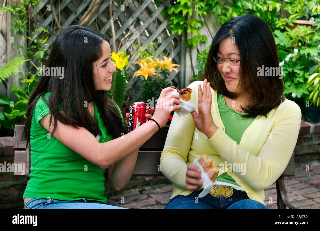 Hispanic American and Korean American girls eating junk food Chicago IL - Stock Image