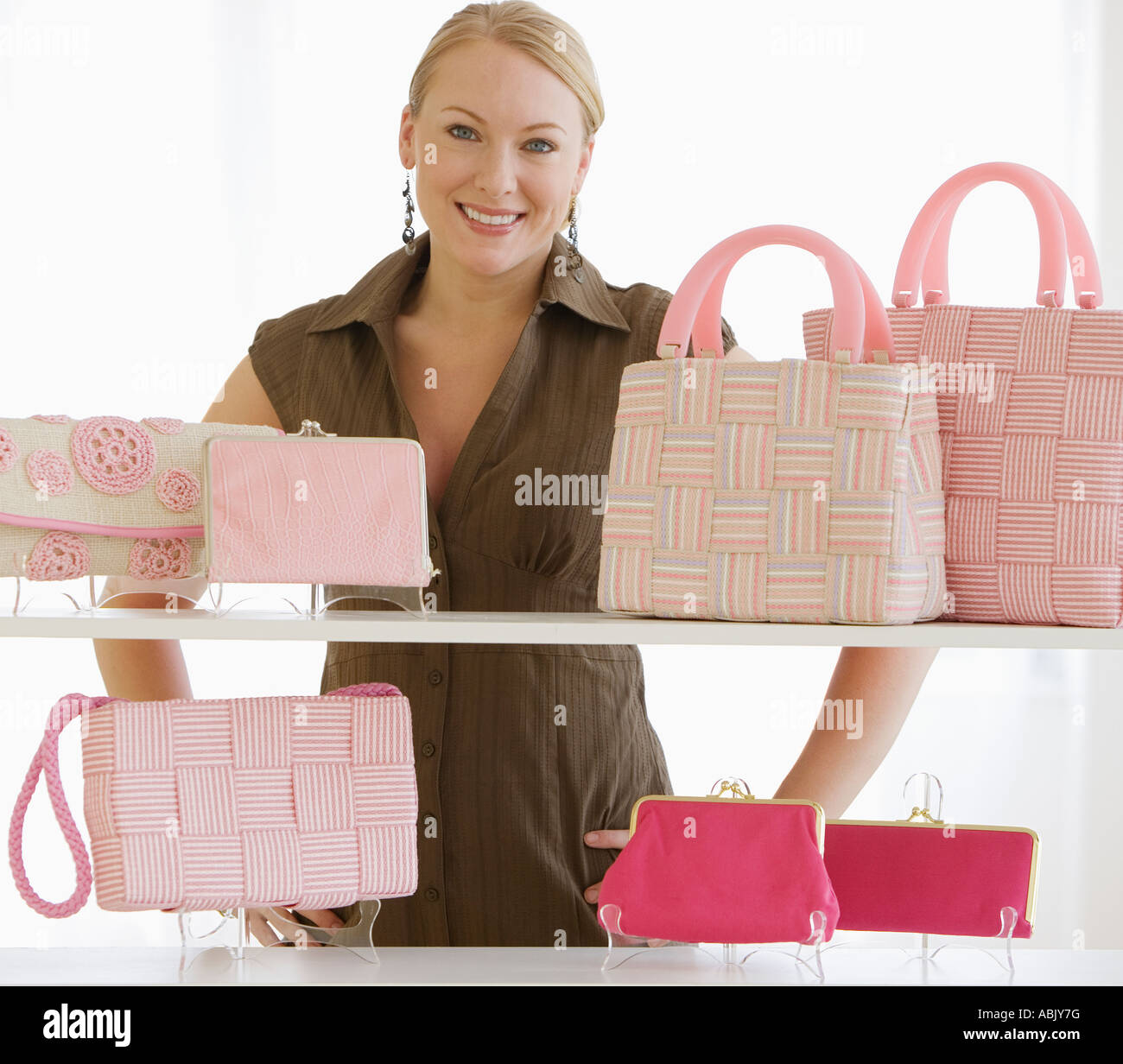Woman behind shelves of purses Stock Photo