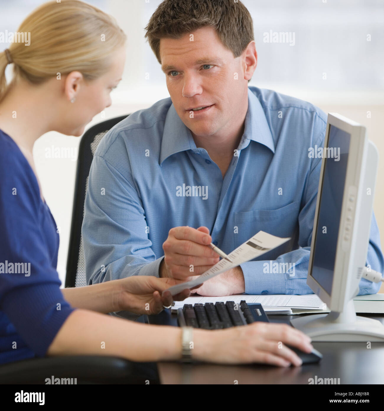 Businesspeople looking at paperwork - Stock Image