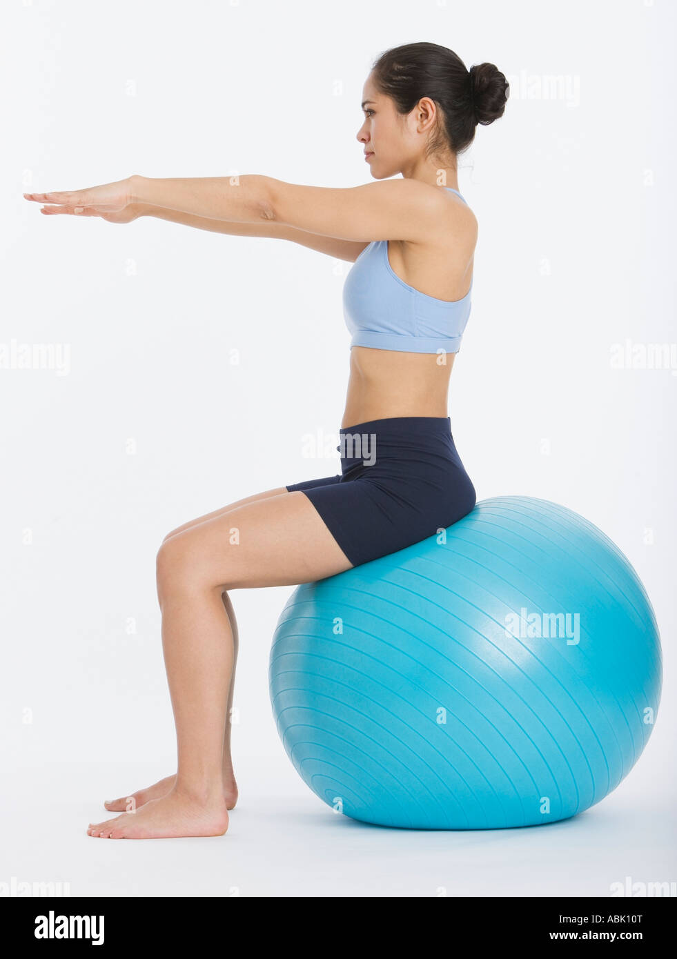 Woman sitting on exercise ball - Stock Image