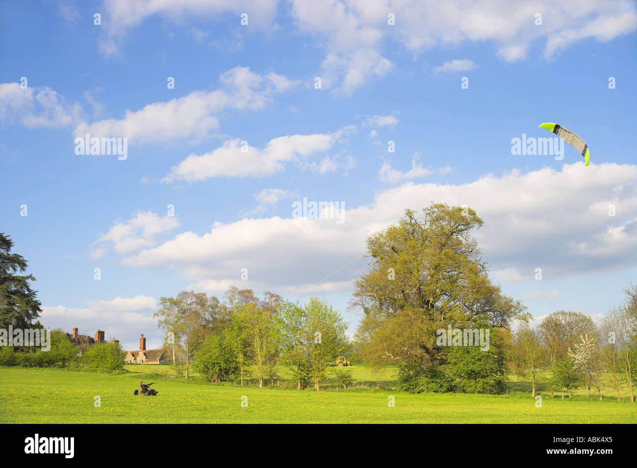 Man flying kite from landboarding buggie above Loseley Park House - Stock Image