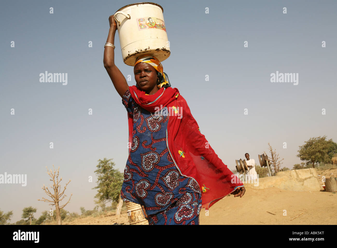A Woman Carrying Water On Her Head, Walking Away From A