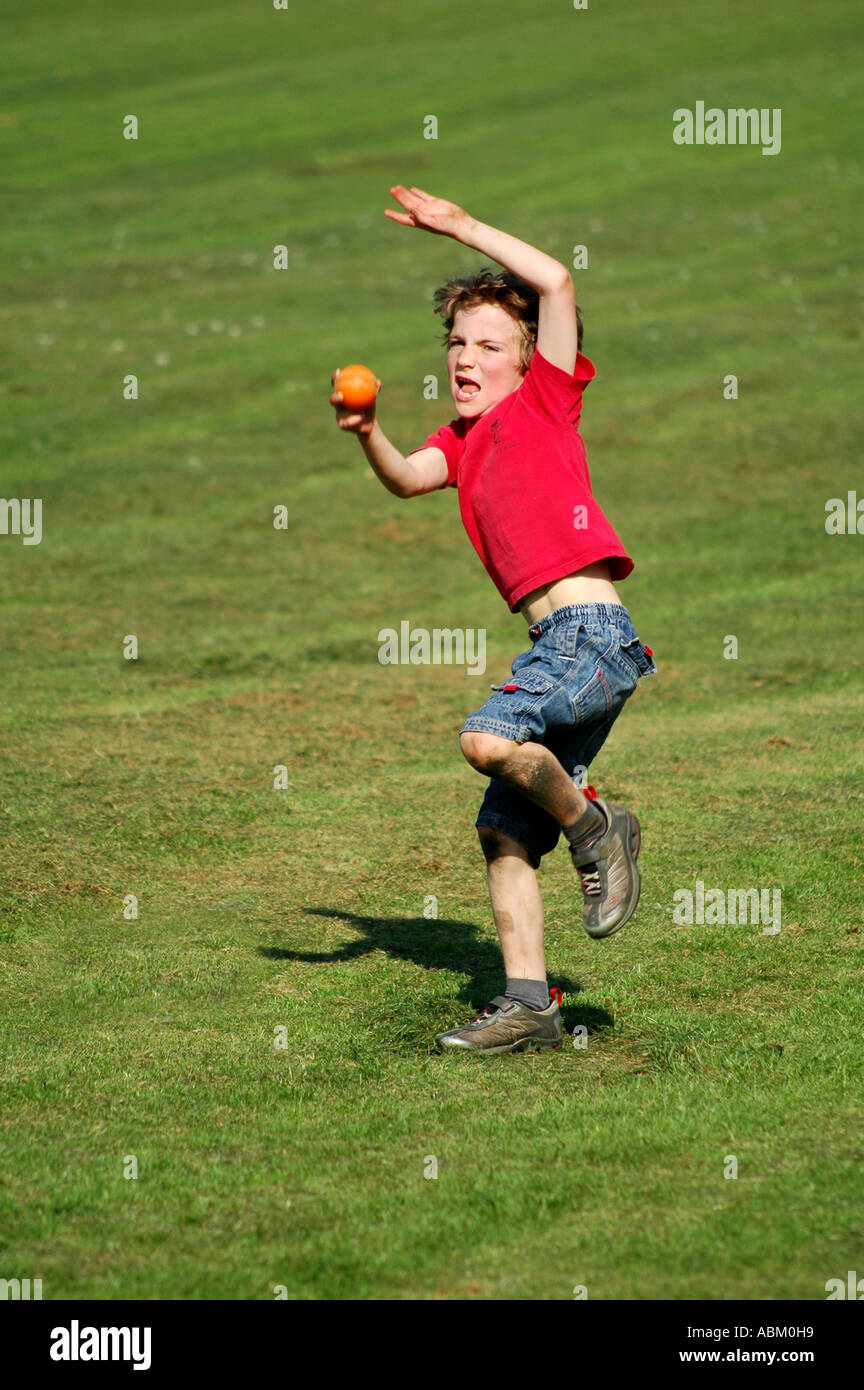 young boy throwing a ball or bowling a cricket ball stock photo  7383064