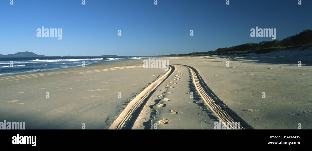 Coastal landscape with tyre tracks on a deserted Australian beach being the only sign of human intrusion - Stock Image