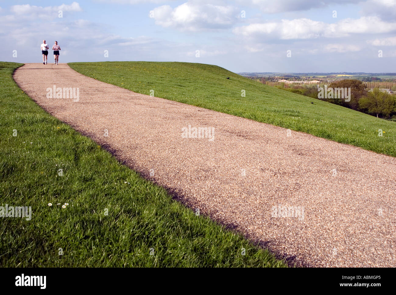 Runners running up a hill in Campbell Park Central Milton Keynes - Stock Image