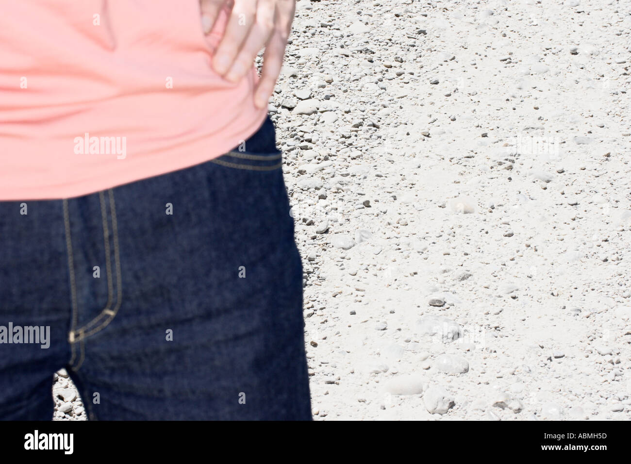 Woman Wearing Blue Jeans Standing On Dirt Road - Stock Image