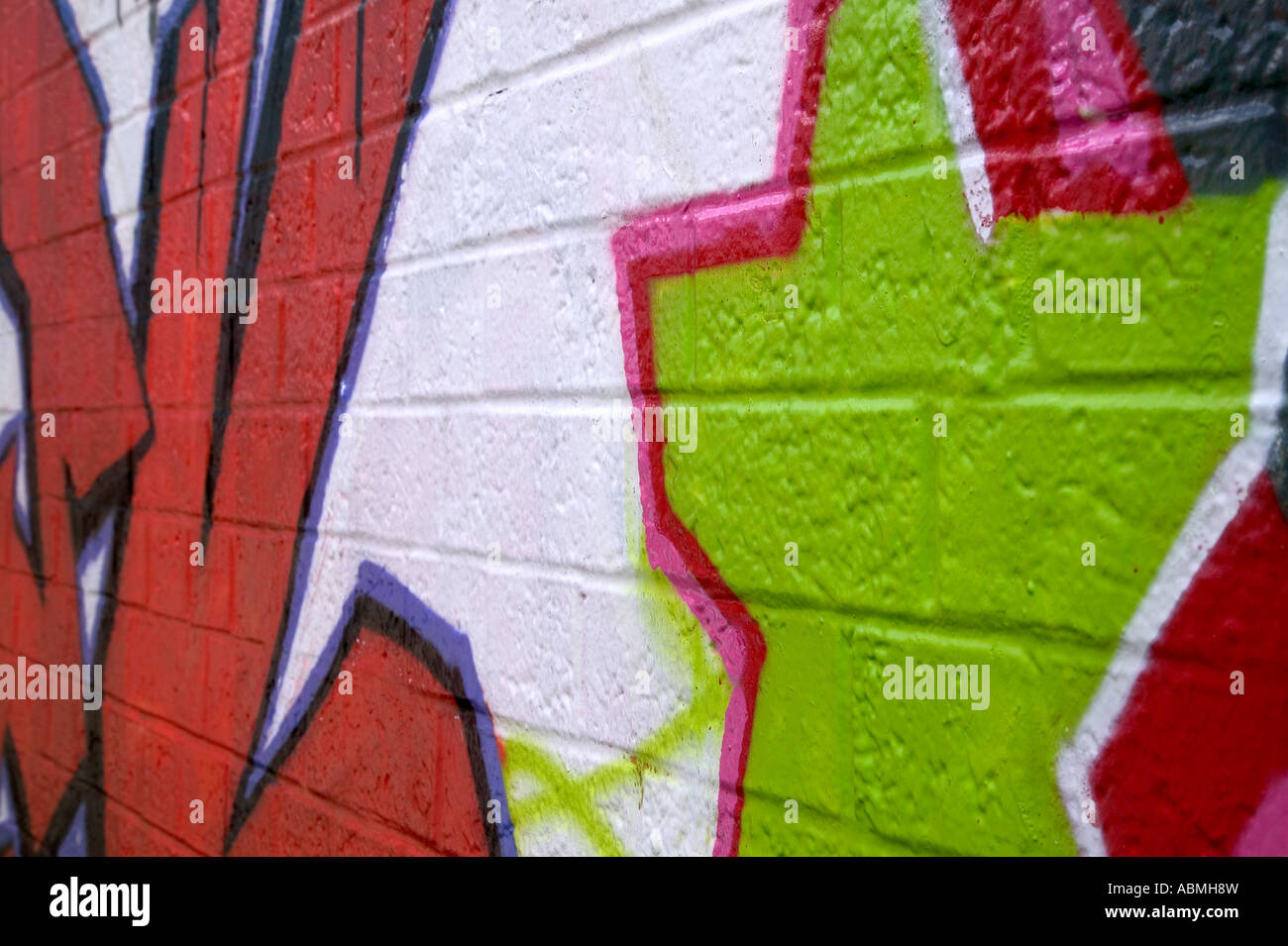 Graffiti sprayed on a brick wall side perspective - Stock Image