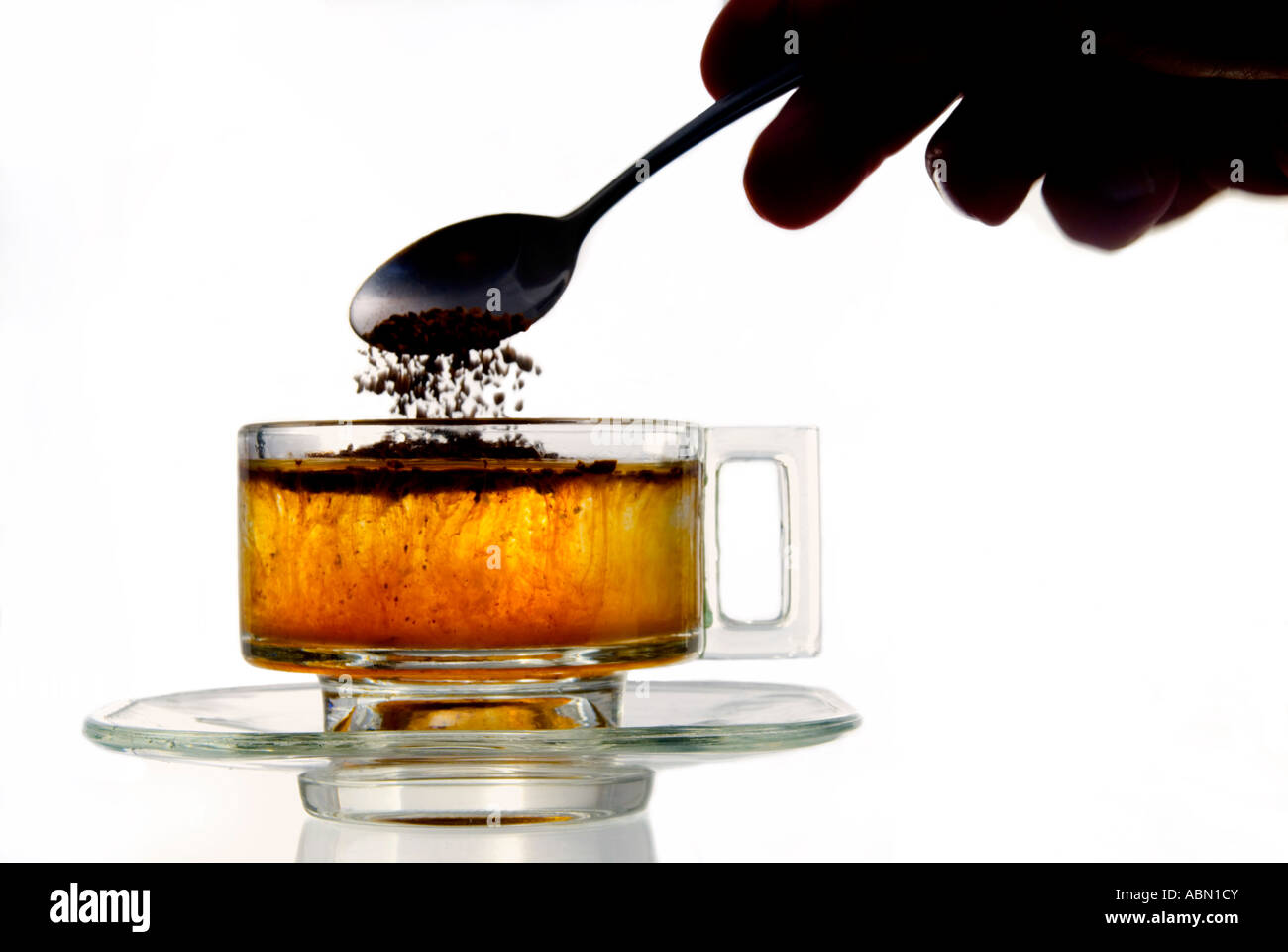 Instant coffee added to water in a glass cup - Stock Image