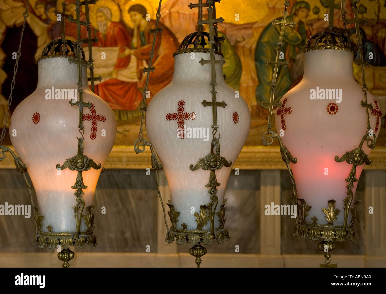 Israel Jerusalem Old City basilica of the Holy Sepulchre the Stone of anointing 3 greek orthodox decorated Alabaster candle holders above the stone with fresque in bkgd - Stock Image