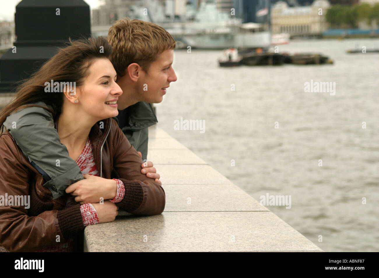 Young couple beside the River Thames in London England Stock Photo