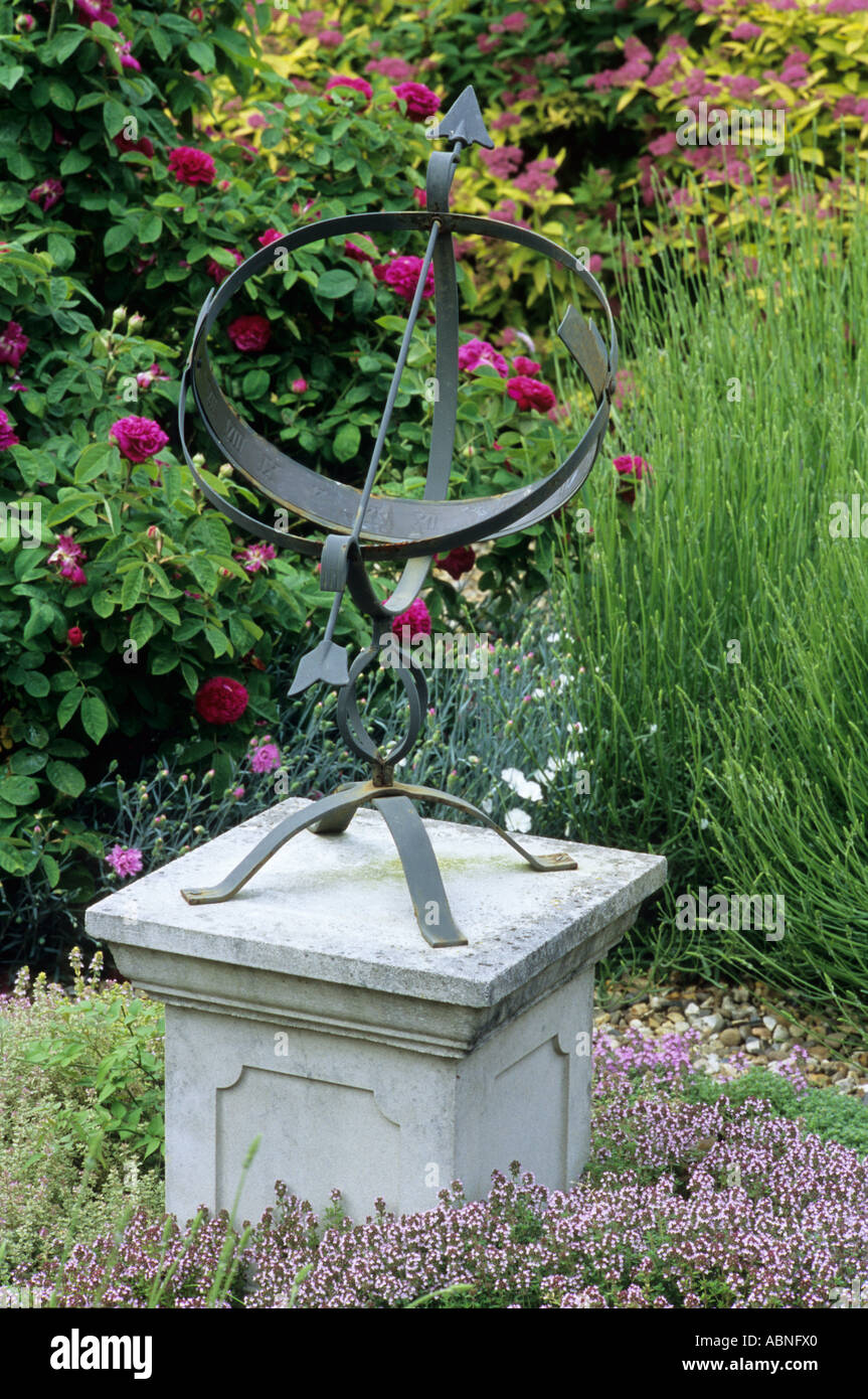 Sundial sundials in garden on stone plinth with Thymus and Roses thyme rose - Stock Image
