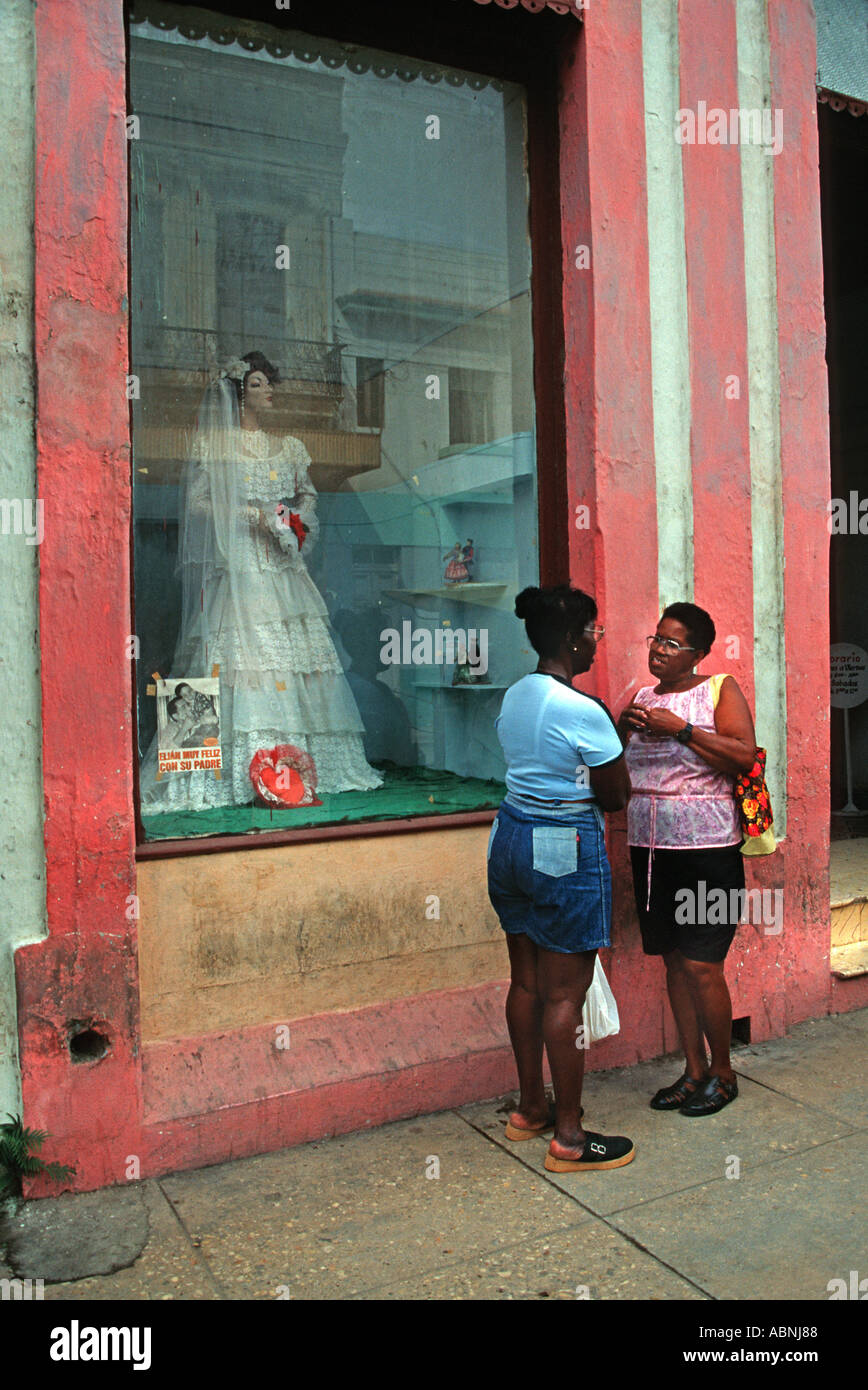 Two Cuban woman standing chatting in the street outside a wedding outfitters Bridal gown in the window of a shop Cardenas Cuba - Stock Image
