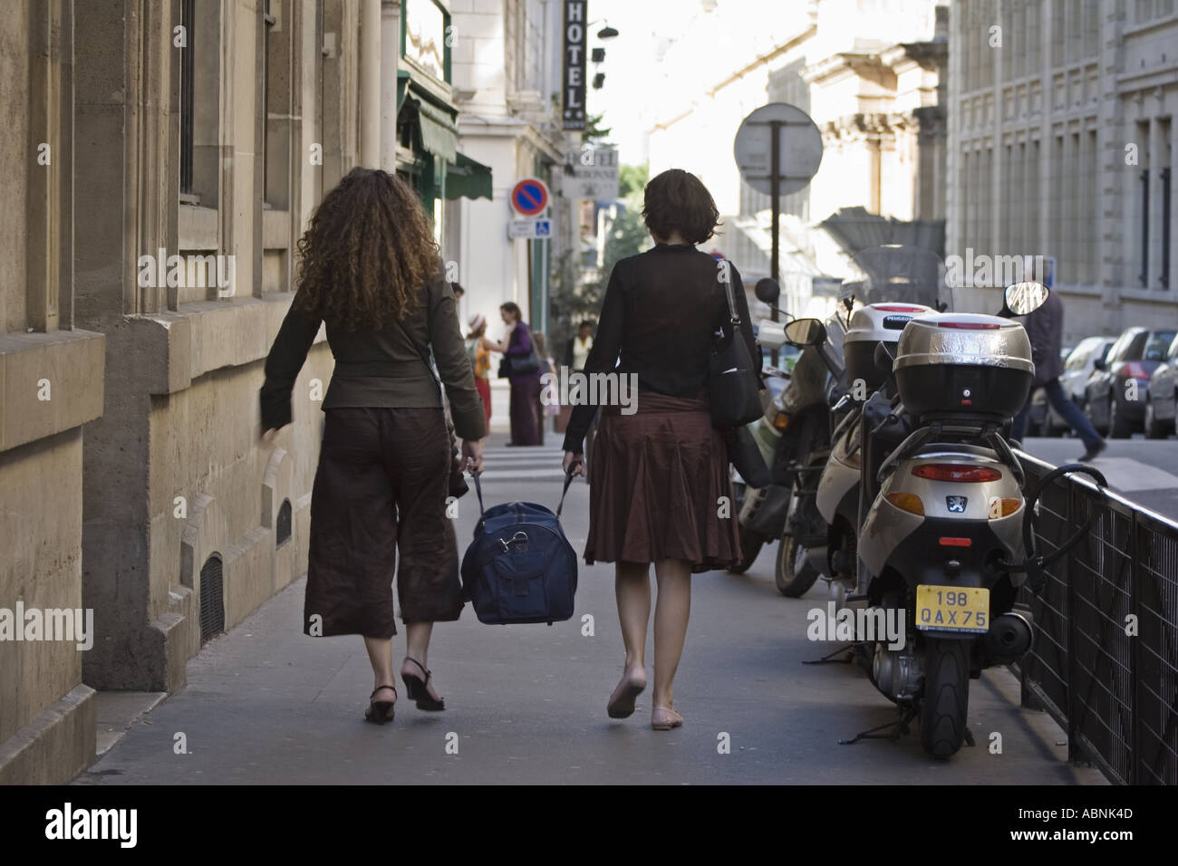 Two women carrying a bag between them near the Sorbonne Paris France - Stock Image