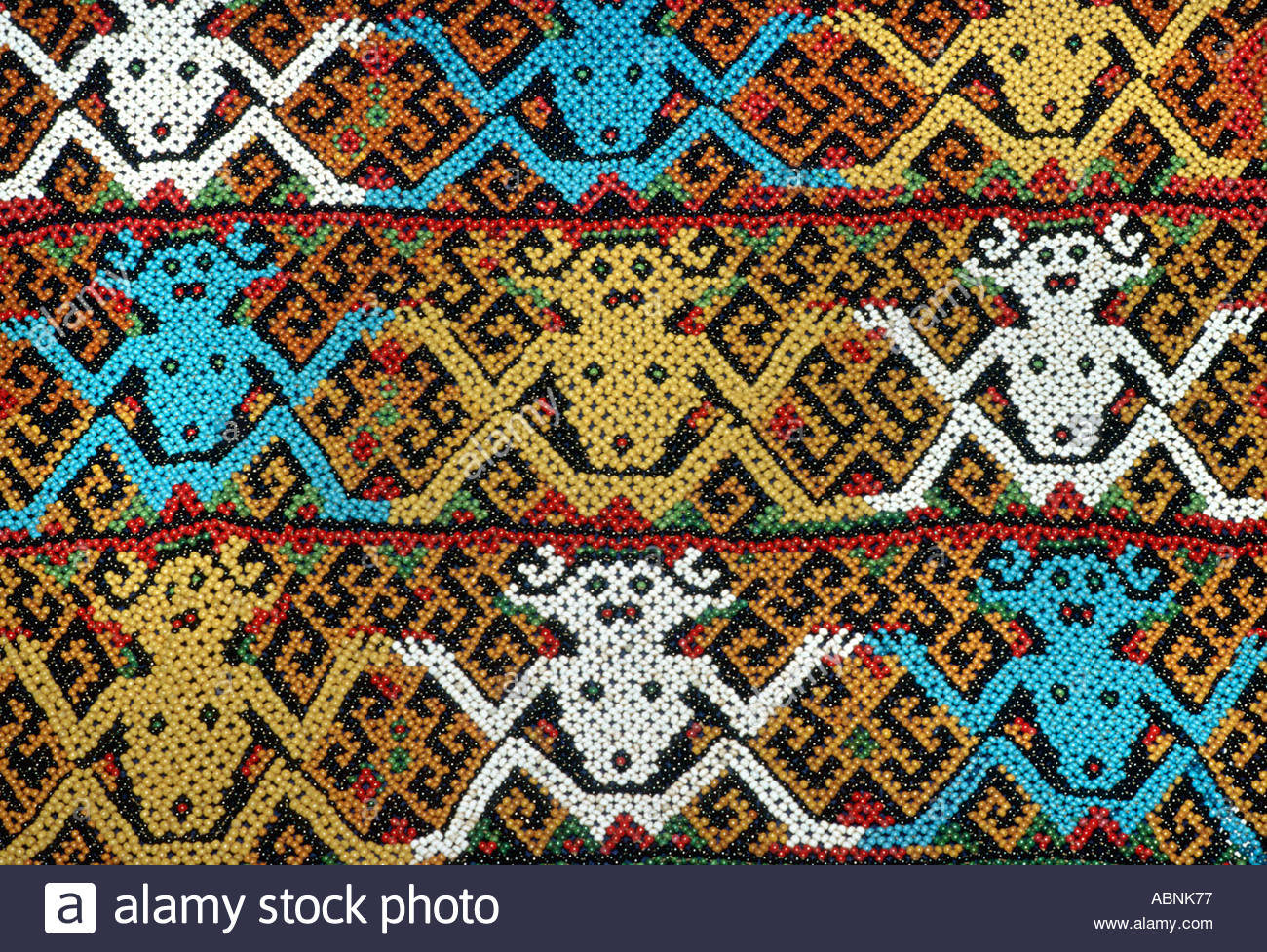 Beadwork textile depicting anthropomorphic motifs Decorating a baby carrier from Borneo Iban people of Kalimantan Stock Photo