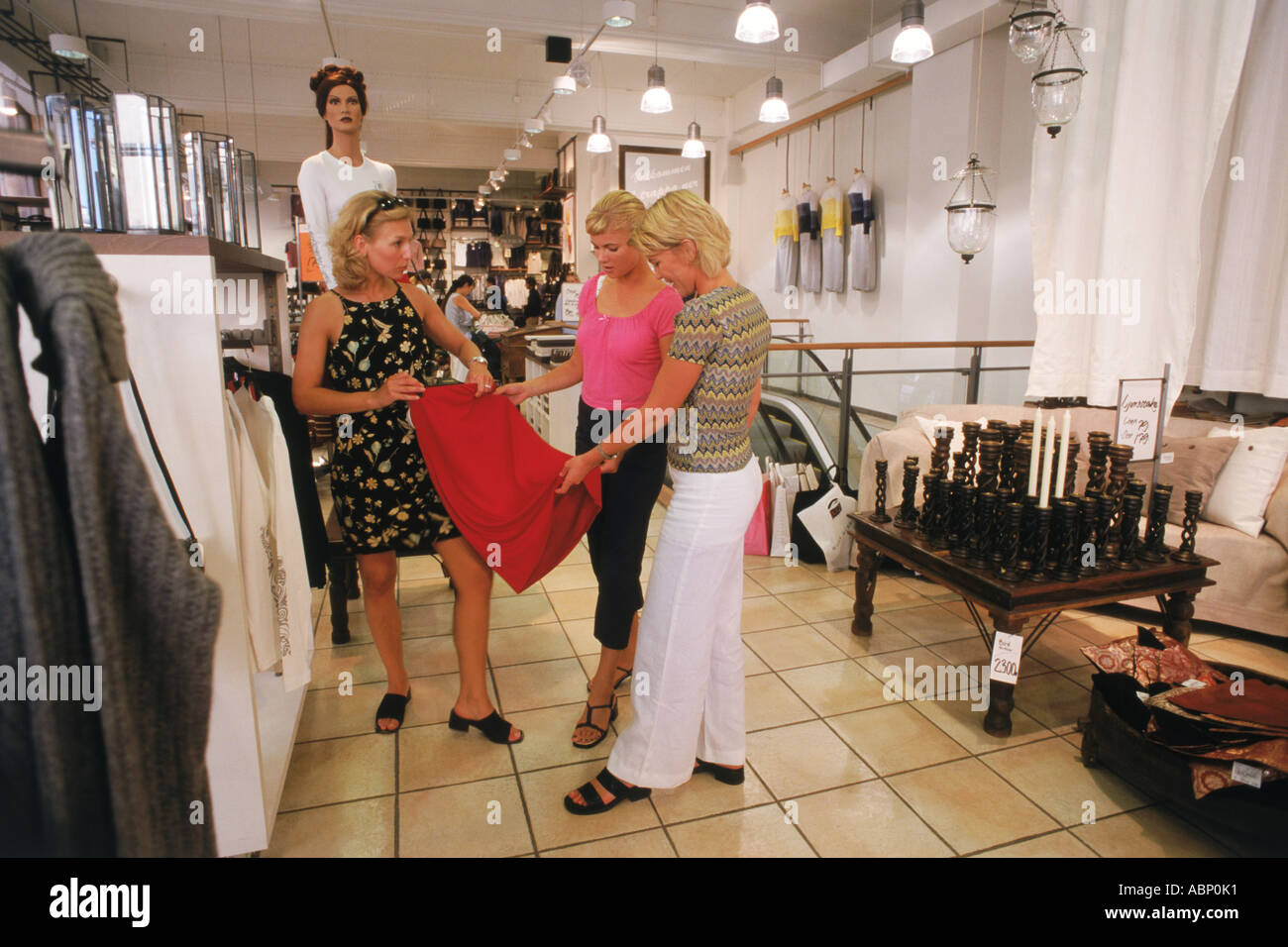 8e2ea0985c6 Three Swedish women shopping together at women's department store in  Stockholm