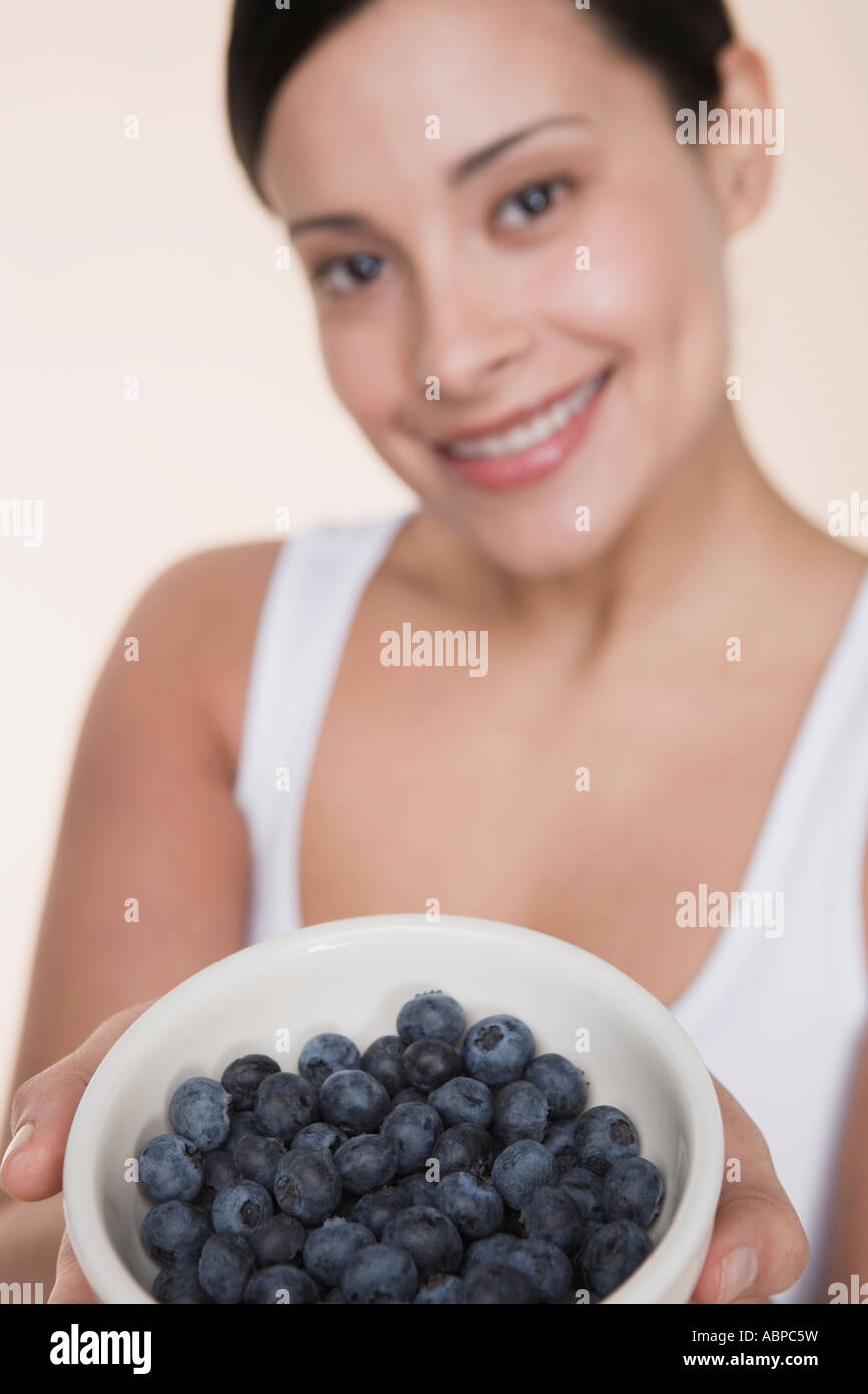 Woman offering bowl of blueberries - Stock Image