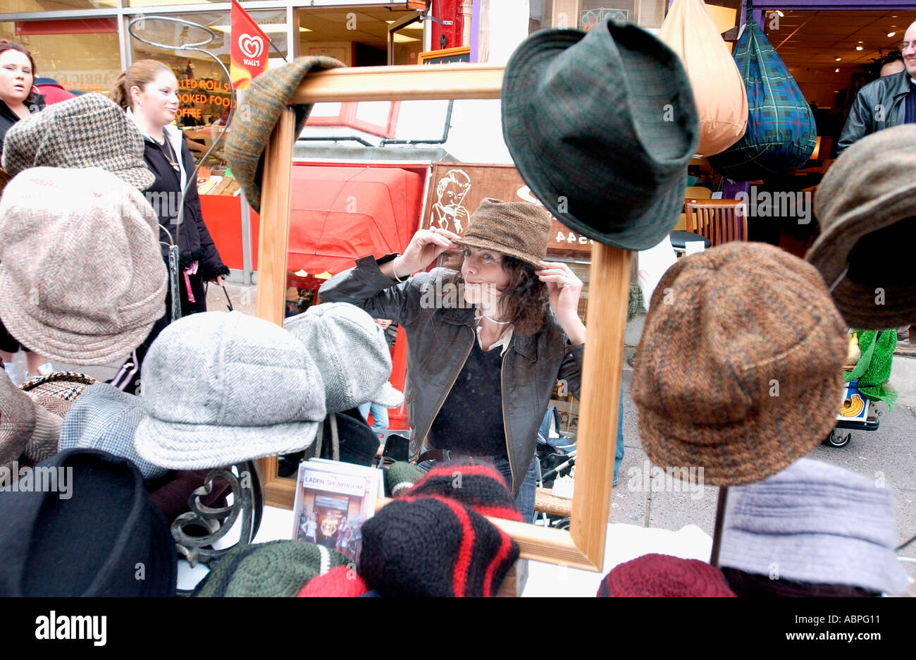 Young woman trying on hat from display of hand made milllinery in a seaside boutique Stock Photo