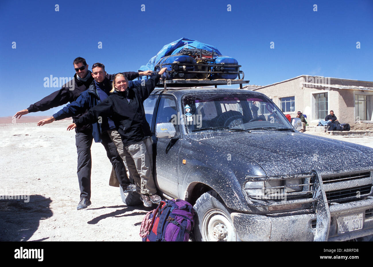 Travellers hanging from their salt bespattered Toyota Landcruiser after a 3 day adventure across the Salar de Uyuni Bolivia - Stock Image