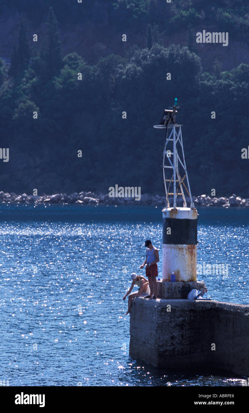 Couple fishing at the end of the harbour arm Poros Kefalonia Ionian Islands Greece Mediterranean Sea - Stock Image