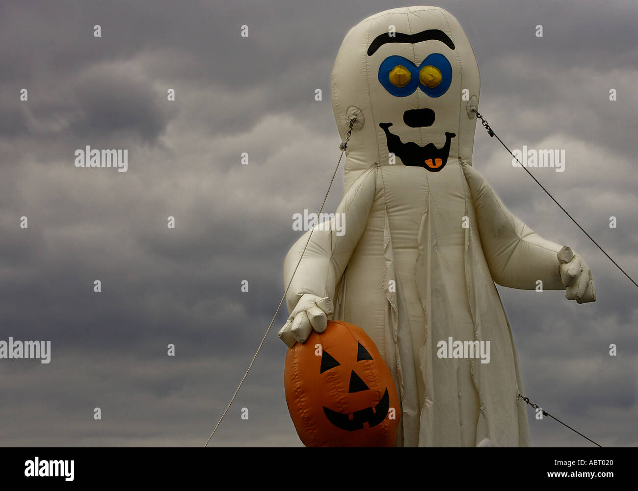 Inflatable ghost holding a Halloween pumpkin - Stock Image