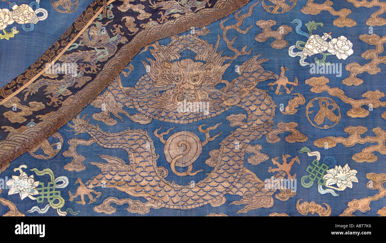 CHINA Detail of a sumptuous dragon robe brocaded with golden threads and silk on an indigo ground Silk tapestry Stock Photo