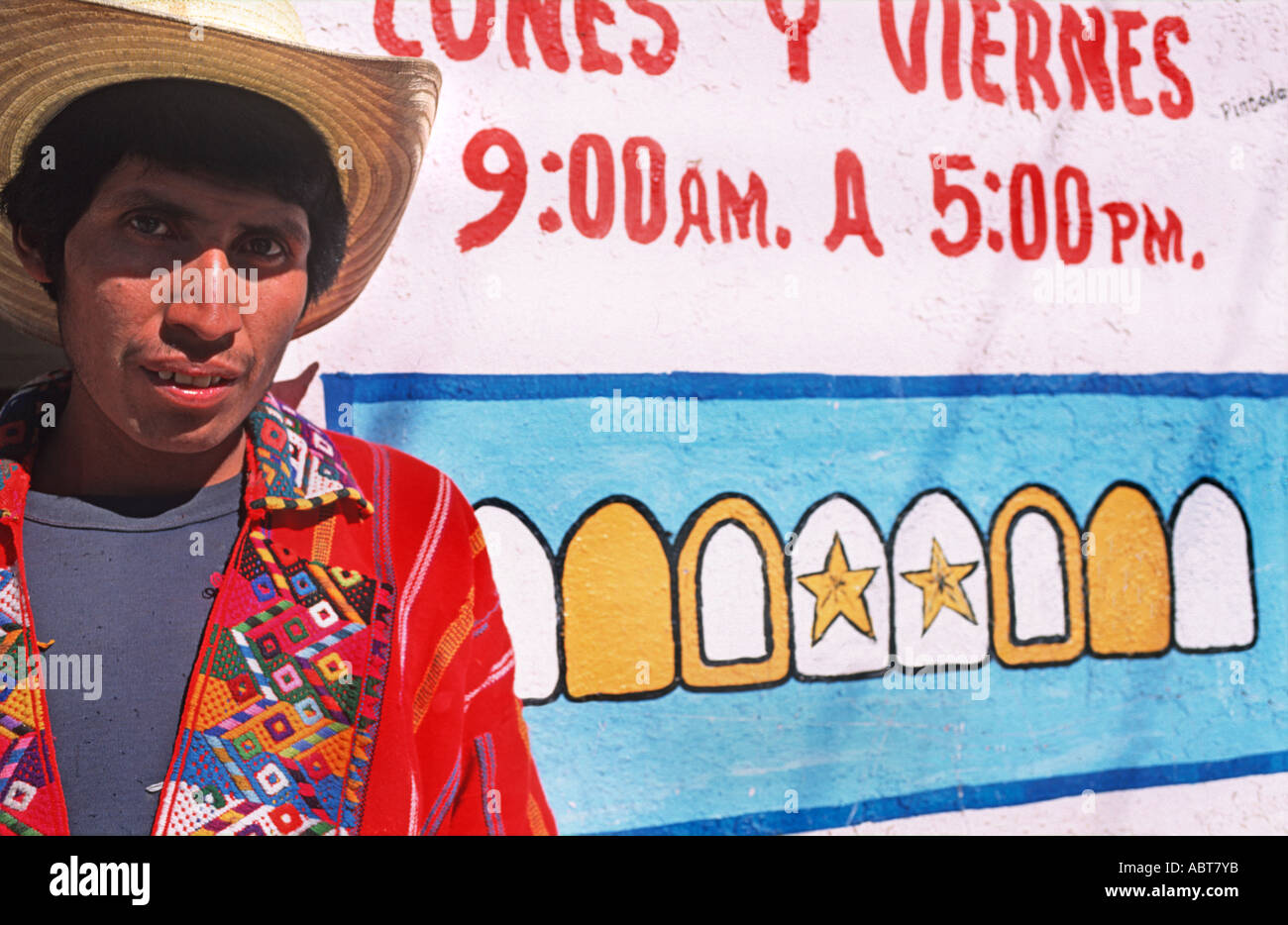 Man from Nahuala standing outside a local dentist Zunil town Guatemala - Stock Image