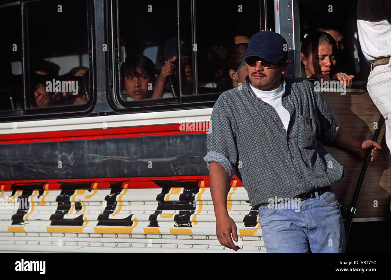 GUATEMALA Guatemalan bus conductor standing at the entrance of a moving bus Central America - Stock Image