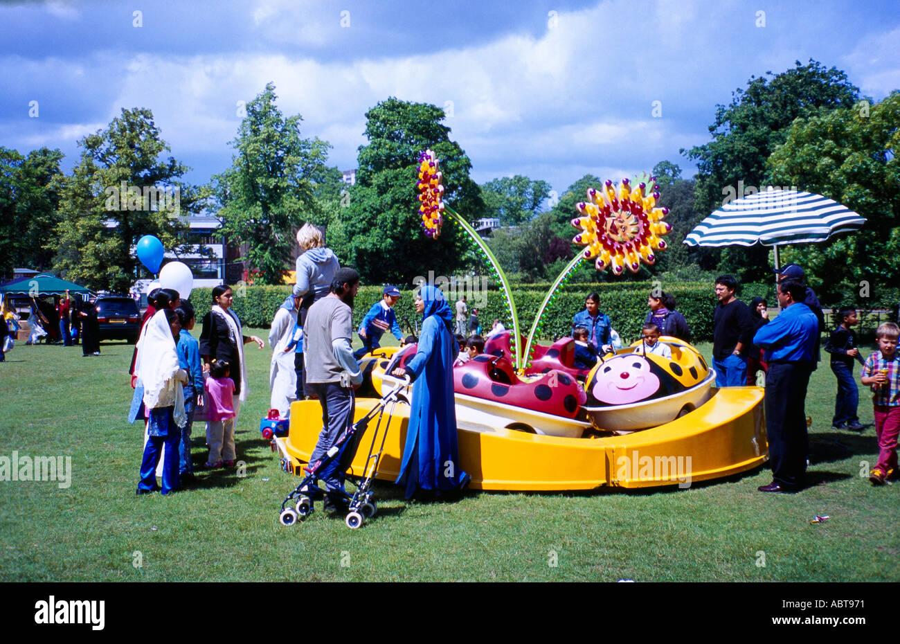 Eid Mela Eid Fair Muslim Families by Roundabout in Birmingham West Midlands England - Stock Image