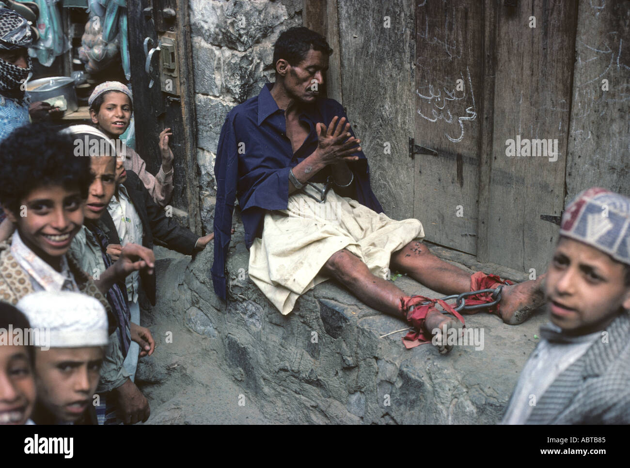 Mentally ill man with legs and wrists in shackles to protect the public Queen Arwa Souk Djibla Yemen - Stock Image