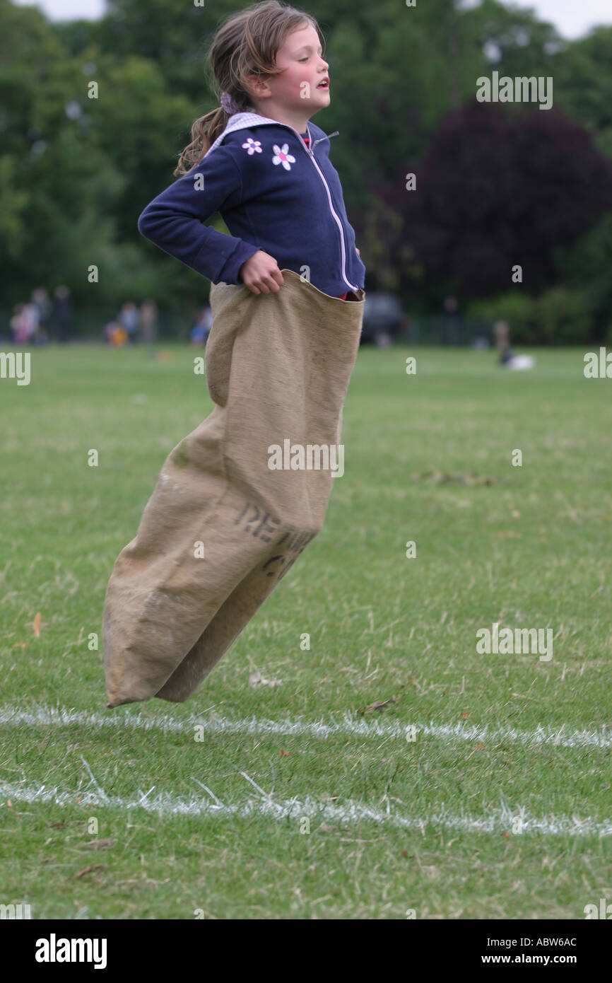A girl jumps in the sack race at her school sports day, London junior school, Clissold park, Stoke newington, London, UK. - Stock Image