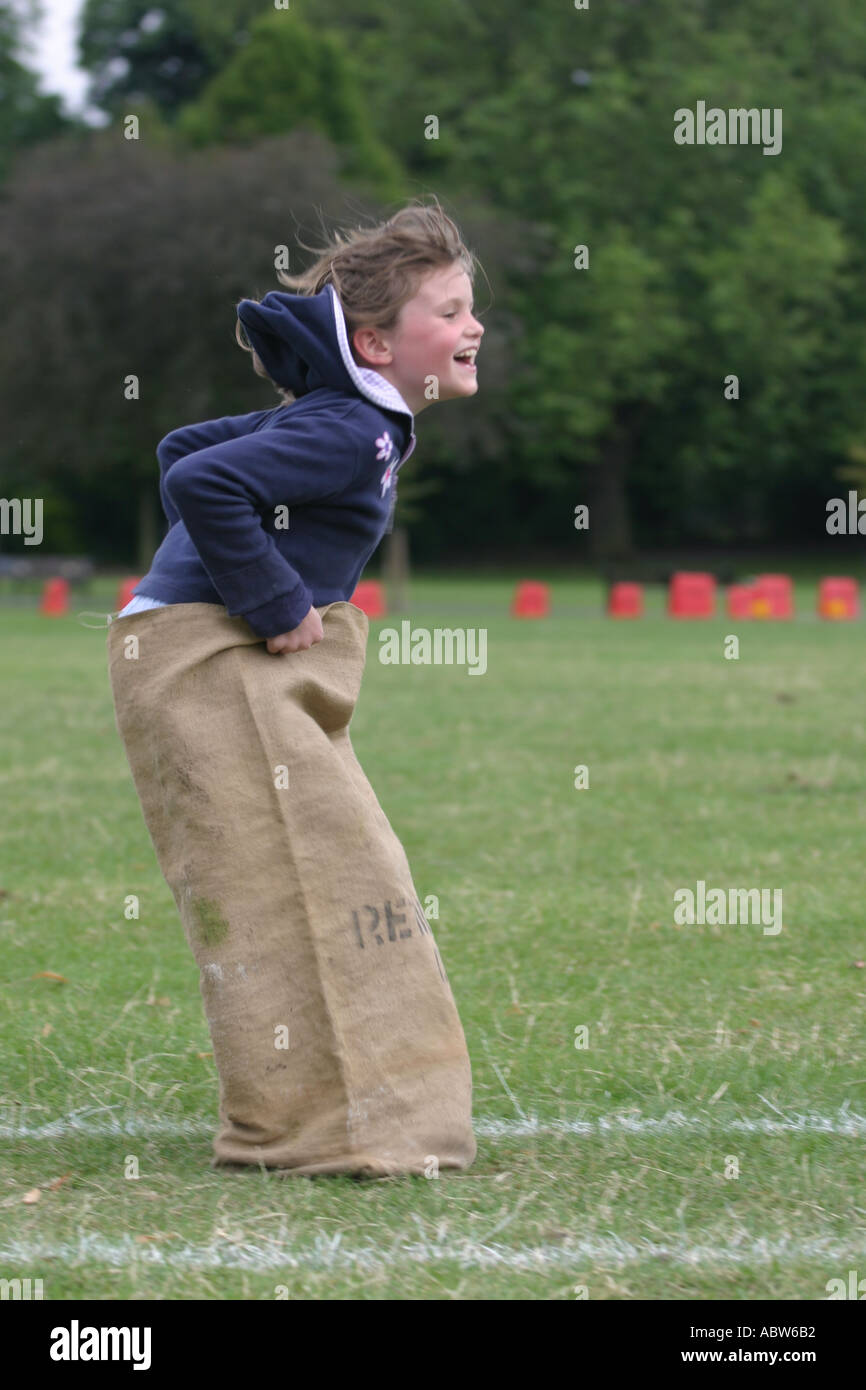 A girl jumps in the sack race at her school sports day, Clissold Park, London, UK. Sequence of 3 images. - Stock Image