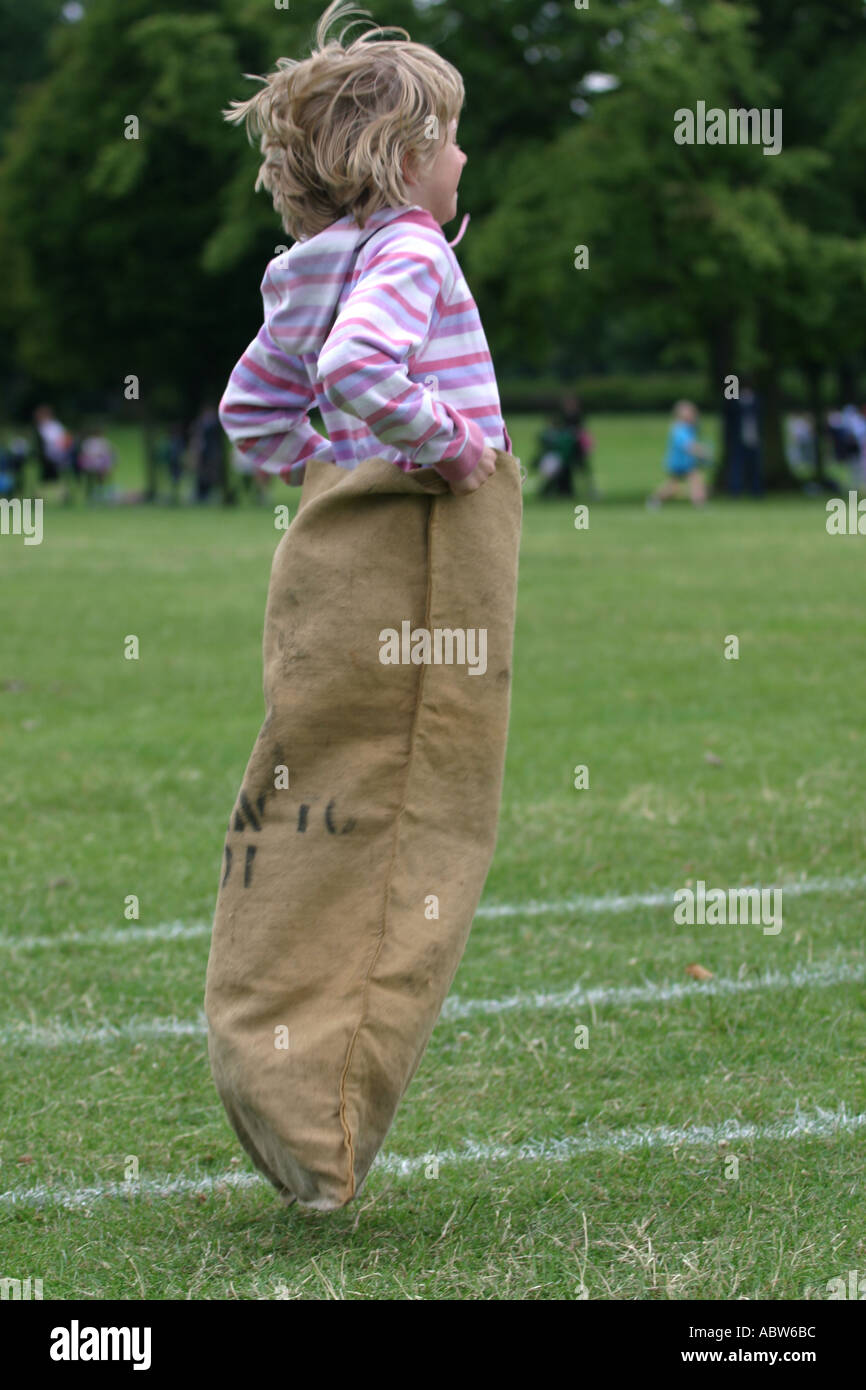 A girl jumps in the sack race at her school sports day, Clissold Park, London, UK. - Stock Image