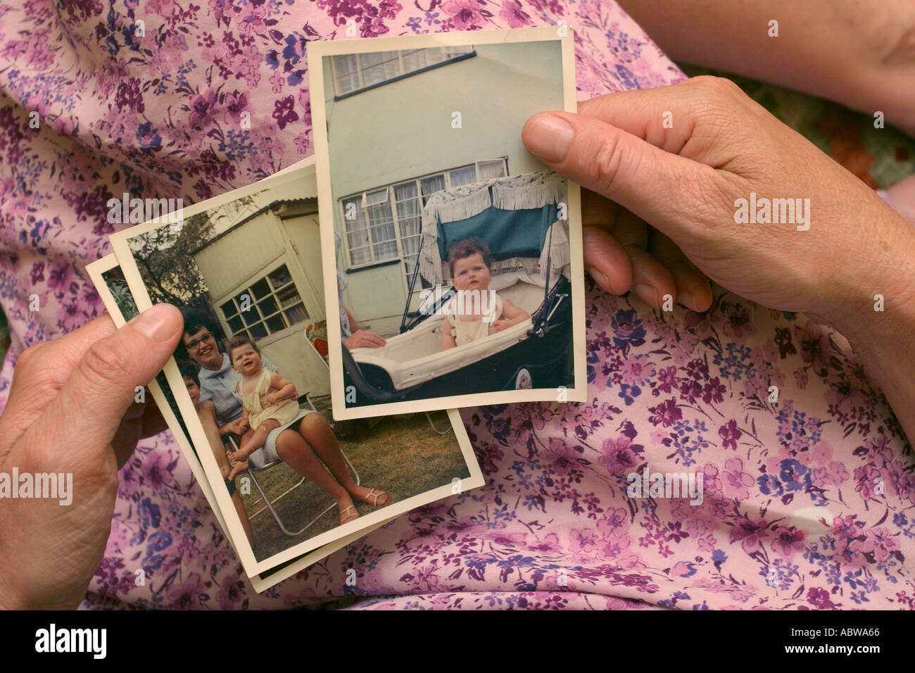A woman holds old photographs of herself when she was a child. - Stock Image