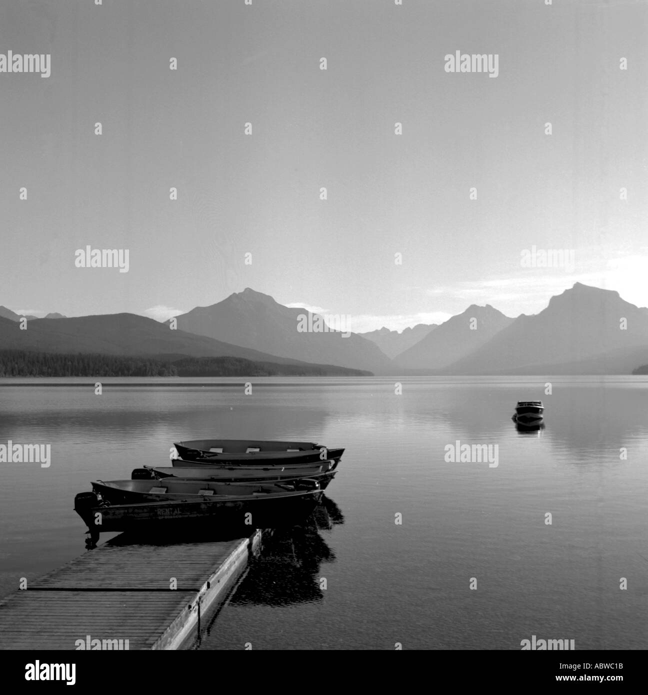 Black and white image of boats on a lake with mountains in the background. - Stock Image