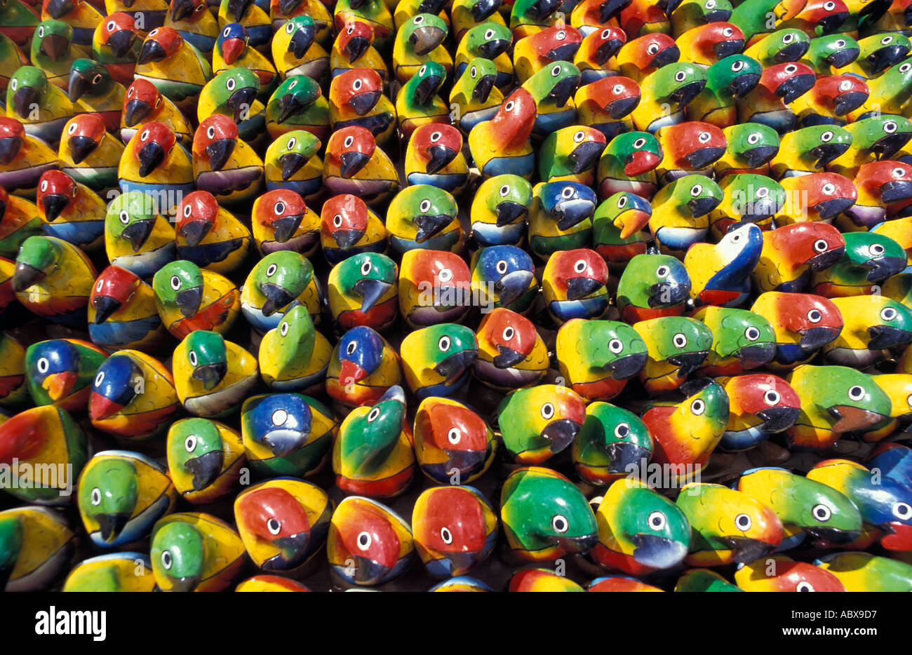 A stall of hand carved and brightly painted wooden parrots Otavalo market Ecuador South America - Stock Image