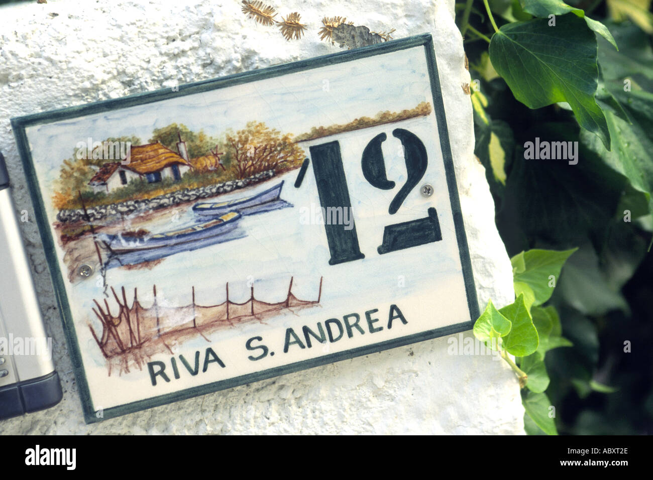 A decorative address plaque on a house in Grado, Italy. - Stock Image