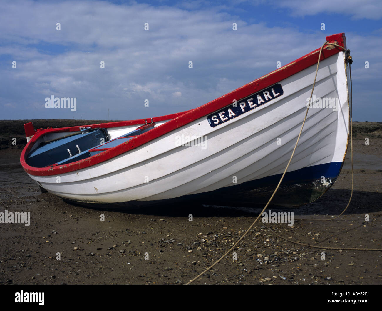 NORFOLK UK March Lone red and white rowing boat left high and dry - Stock Image