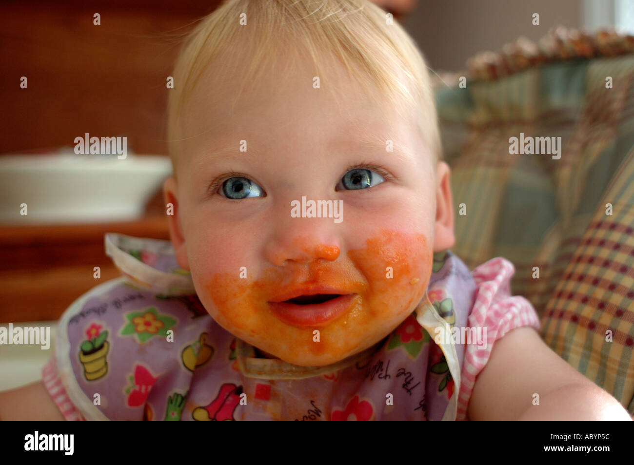 baby toddler child one 1 eating feeding eat feed lunch supper dinner snack sauce tomato sauce highchair high chair tray messy t - Stock Image