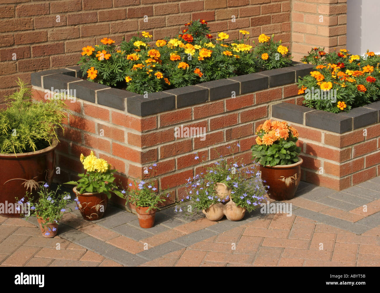 Summer Flowers In A Raised Bed With Pots On A Patio