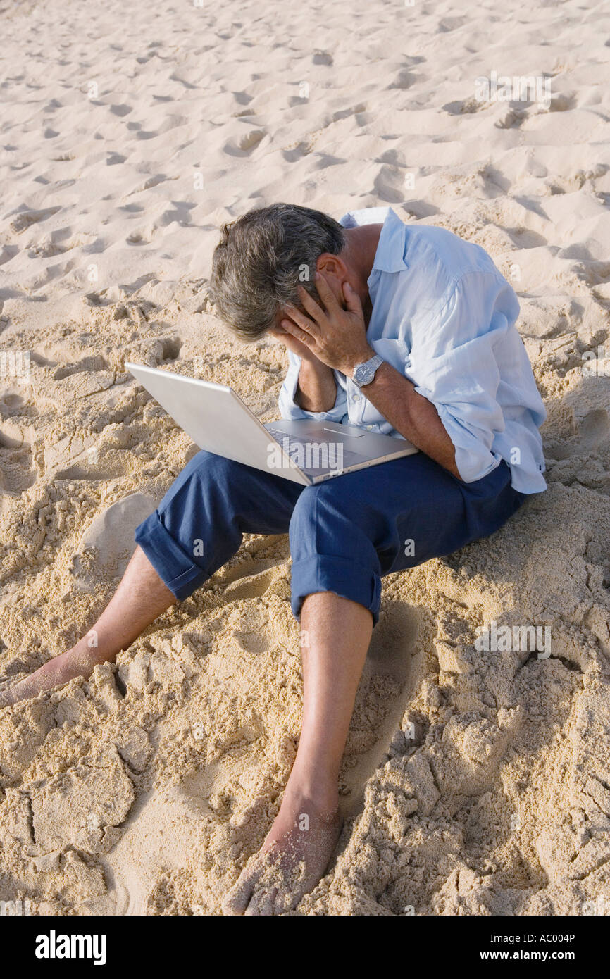 Dejected man using laptop on beach - Stock Image